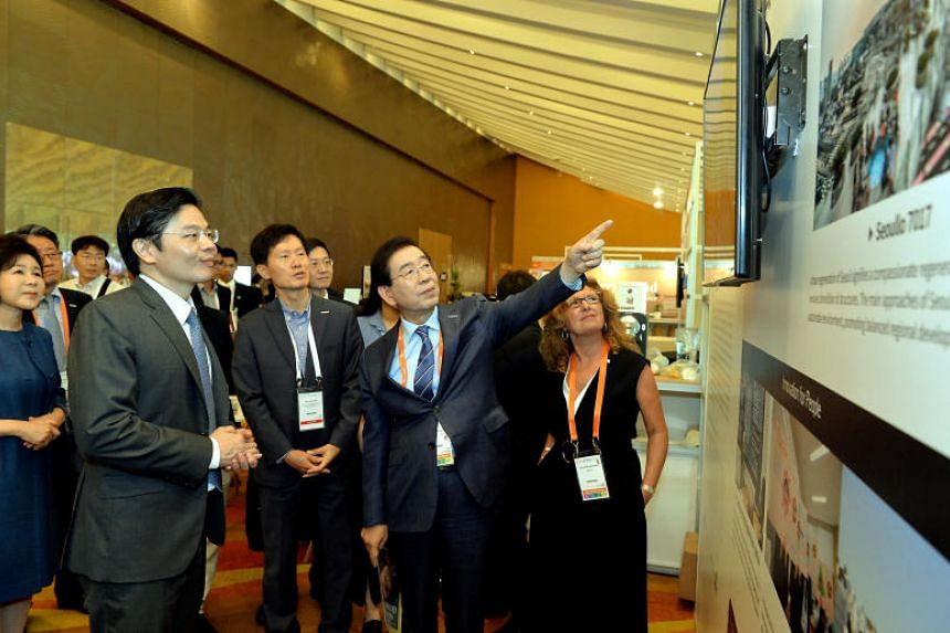 Minister for National Development Lawrence Wong (left) touring the Seoul booth with Seoul Mayor Park Won-soon at the World Cities Summit on July 8, 2018.
