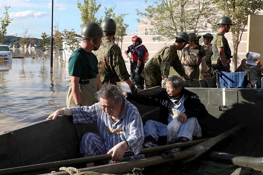 Staff and patients, some still in their pyjamas, being rescued from Kurashiki city's isolated Mabi Memorial Hospital in rowboats yesterday. A flooded area in Kurashiki, Okayama Prefecture, taken by Kyodo yesterday. The city with a population of just