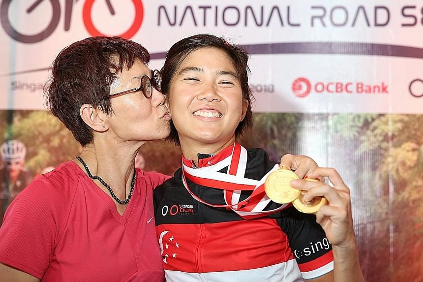 The race terrain in Nongsa, Batam, where 264 cyclists competed across 12 categories at the OCBC Cycle National Road Championships yesterday. Below: Women's Open champion Serene Lee, 30, with her mother after the presentation ceremony. She won her fir