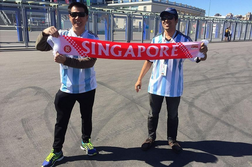 Kenny Cheong and his wife Annabelle Tan at Fisht Olympic Stadium in Sochi. He said the highlight of their trip was watching the 3-3 draw between Spain and Portugal. Below: Long-time friends Tilak Dasgupta and Richard Tan at Saint Petersburg Stadium.
