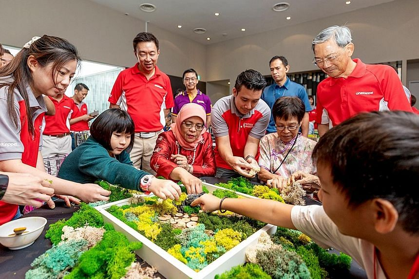 President Halimah Yacob (centre, seated), Keppel Corporation chairman Lee Boon Yang (right, standing) and Keppel CEO Loh Chin Hua (third from left, standing), join Keppel's beneficiaries from Monfort Care and Care Corner in a moss art activity.