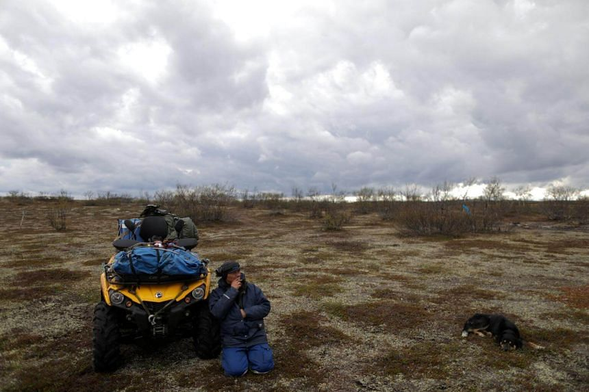 Sami reindeer herder Nils Mathis Sara sheltering from the wind as he smokes next to his ATV in the Finnmark Plateau, Norway, on June 15, 2018.