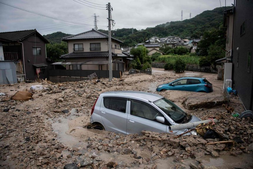 Cars trapped in the mud after floods in Saka, Hiroshima prefecture, on July 8, 2018. Dozens of people remain missing after the days of torrential rains that have caused flash floods and landslides.
