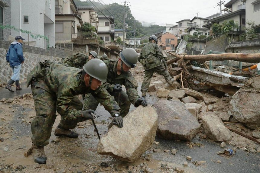 Japanese Self-Defense Forces rescuers removing stones scattered by debris flow in Hiroshima. The death toll in the devastating rains have risen to 75, on July 9, 2018.