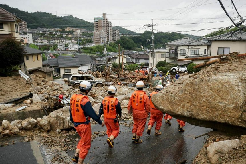 Hiroshima fire department rescue workers search for missing people at a landslide-devastated residential area on July 8, 2018.