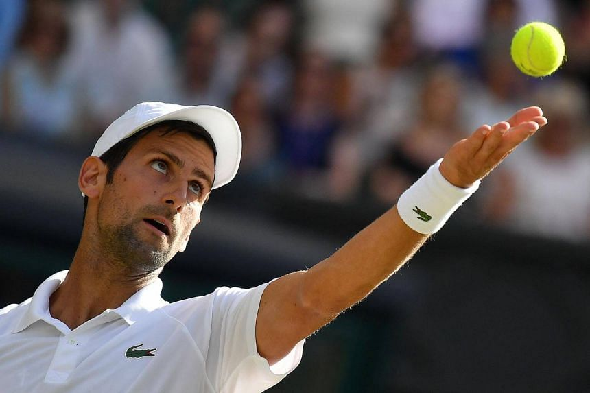 Serbia's Novak Djokovic throws the ball to serve during his men's singles third round match on the sixth day of the 2018 Wimbledon Championships at The All England Lawn Tennis Club in Wimbledon, on July 7, 2018.