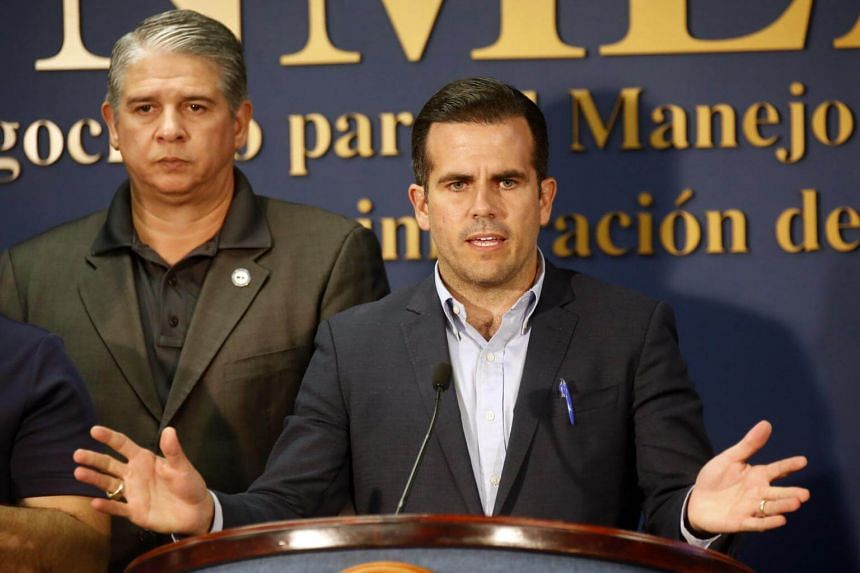 Governor of Puerto Rico Ricardo Rossello (right) speaking during a press conference at the Bureau for Emergency Management and Disaster Management in San Juan, Puerto Rico, on July 6, 2018.