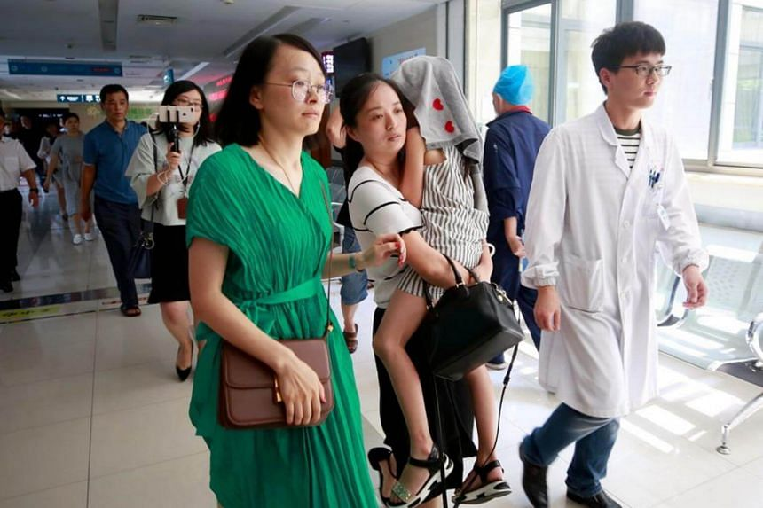 A young survivor of the boat tragedy in Thailand is carried into Haining People's Hospital in Haining, Zhejiang province, for a follow-up medical check.