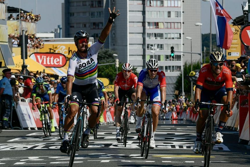 Slovakia's Peter Sagan celebrates after winning from Italy's Sonny Colbrelli (right) and France's Arnaud Demare (second from right) the second stage of the Tour de France between Mouilleron-Saint-Germain and La Roche-sur-Yon on July 8, 2018.