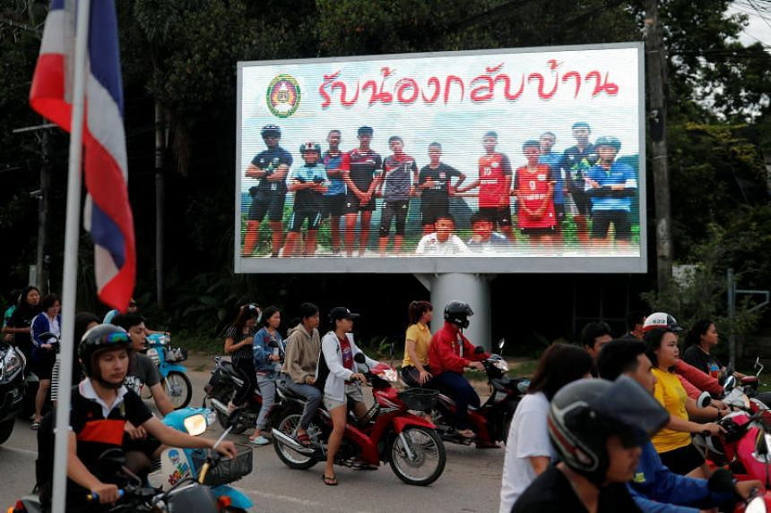 """A board saying """"Welcome home, boys"""" is seen in Thailand's Chiang Rai province on July 9, 2018, after rescue operations began for the 12 schoolboys and their football coach trapped in Tham Luang cave."""
