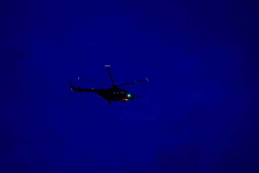 A military helicopter believed to be carrying one of the schoolboys evacuated from Tham Luang cave taking off from the area on July 9, 2018, during ongoing rescue operations.