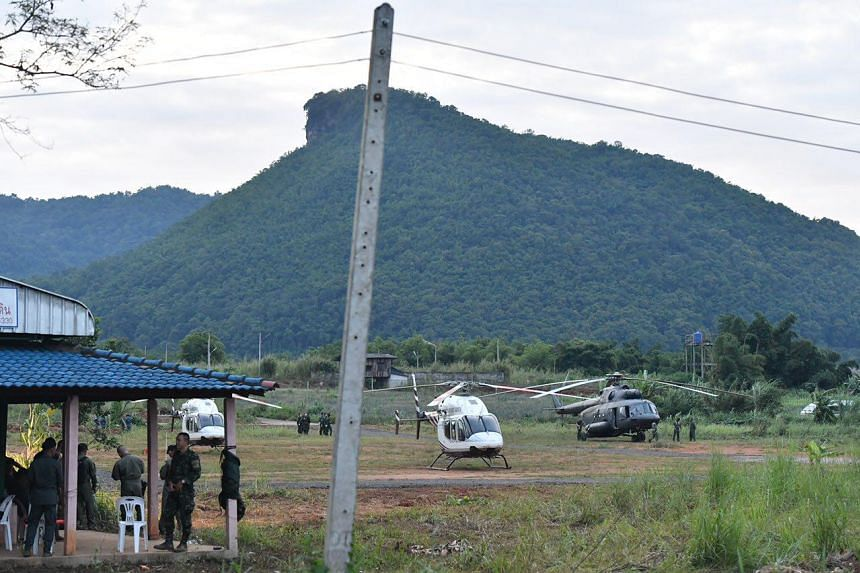 Helicopters stand by at a temporary pad near Tham Luang cave on July 9, 2018, during ongoing operations to rescue the remaining schoolboys and their football coach trapped inside the cave.