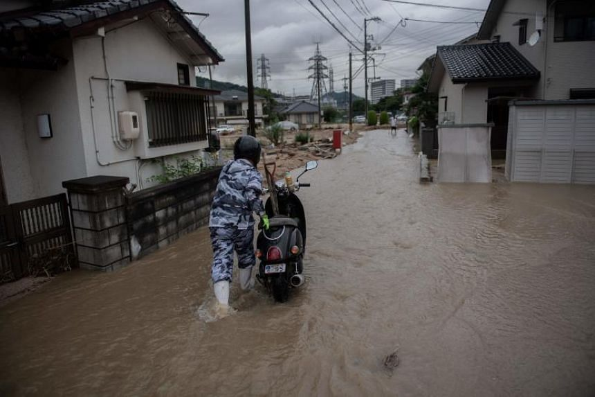A man pushes his scooter through a flooded street in Saka, Hiroshima prefecture, on July 8, 2018.