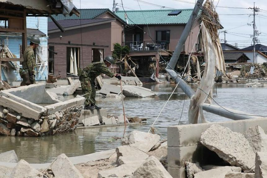 Soldiers search for victims at a flood hit area in Kurashiki city, Okayama prefecture, on July 9, 2018.