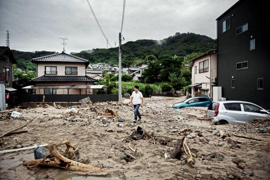 A man walks past a devastated street during floods in Saka, Hiroshima prefecture, on July 8, 2018.