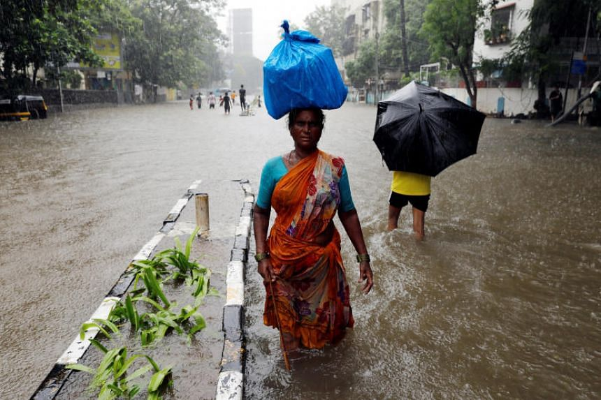 People wading through a waterlogged street during heavy rains in Mumbai, India, on July 8, 2018.