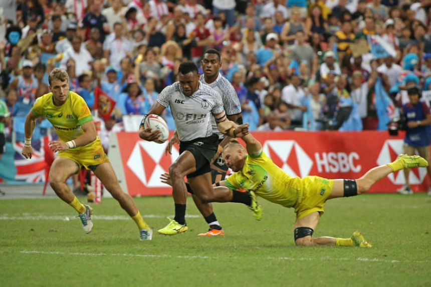 Fiji's Amenoni Nasilasila (centre) skips past Australia's Tom Connor during the HSBC Singapore Rugby Sevens final at the National Stadium on April 29, 2018.