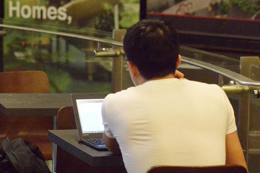 File photo showing a man using a laptop at a cafe. Singapore agreed to add new border enforcement measures to deal with goods infringing intellectual property rights.