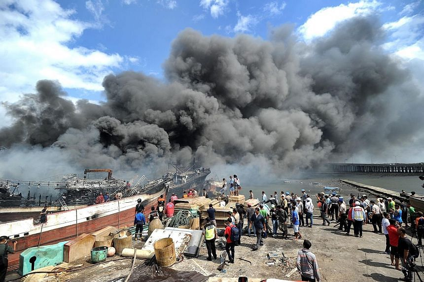 Workers and firefighters trying to extinguish a fire on fishing boats at Benoa harbour on Indonesia's resort island of Bali yesterday. The fire started after midnight and quickly engulfed nearly 40 local vessels but no injuries have been reported.
