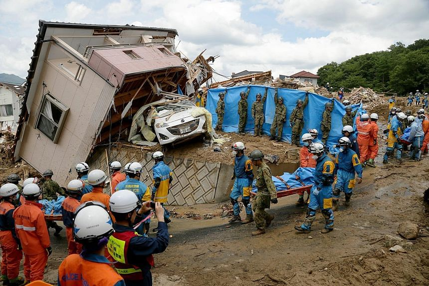 Japanese police and Self-Defence Force workers carrying a victim killed by a landslide caused by heavy rain in Kumano, Hiroshima prefecture, yesterday. Over 74,000 personnel, including police officers, firefighters and Self-Defence Force soldiers, ha