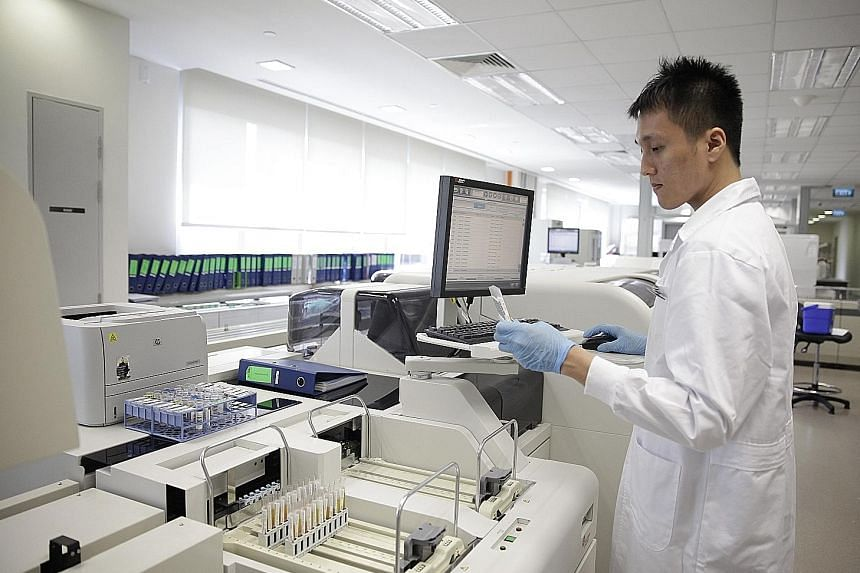 Medical lab technologist Su Jun Qiang, 27, verifying a glucose test result at the Clinical Biochemistry Laboratory under Singapore General Hospital's Department of Clinical Pathology.