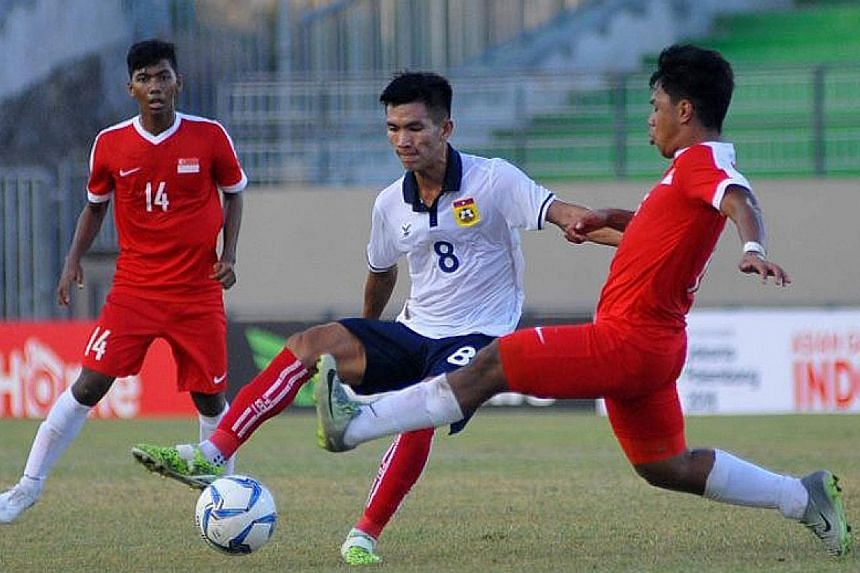 Singapore U-19 defender Nur Adam Abdullah tries to tackle Laos midfielder Chanthachone Thinolath in the Cubs' 5-0 defeat.