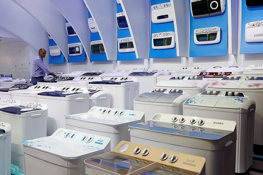 """Washing machines at a fair in Guangzhou, China. Direct US tariffs affect a relatively small set of Singapore products - namely solar cells and modules, washing machines, steel and aluminium. These exports account for a """"relatively modest"""" 0.1 per cen"""