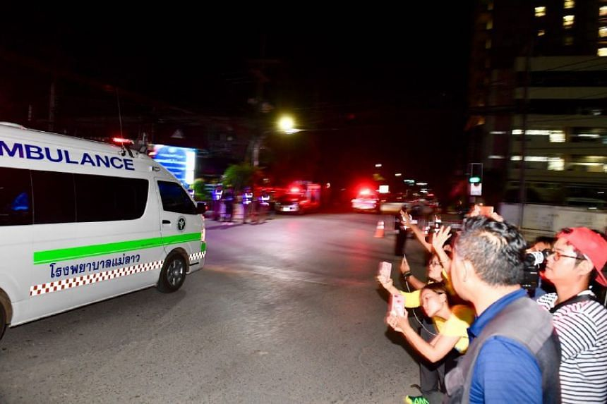 The last ambulance drives past the media and onlookers into the entrance of the hospital amidst loud cheers and applause from the locals.