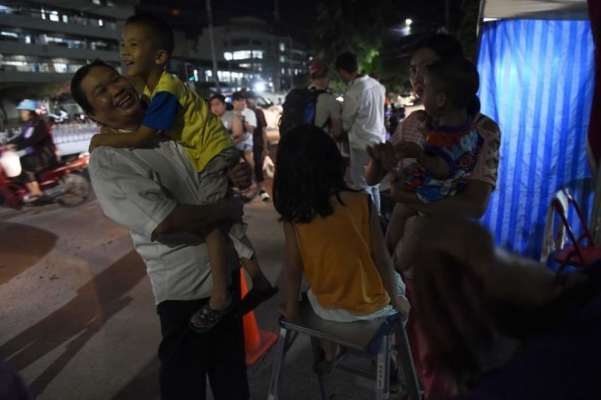 People react near a hospital, where the children's football team members are treated after being rescued, in Chiang Rai on July 10, 2018.