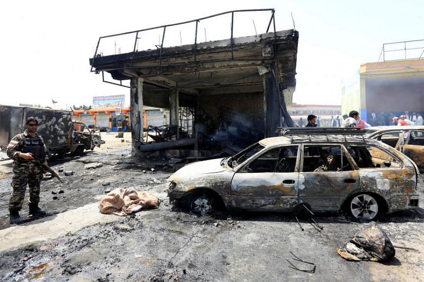 Afghan security forces inspect the site of a suicide attack in Jalalabad on July 10, 2018.