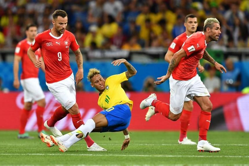 Brazil's forward Neymar (centre) falls during the Russia 2018 World Cup Group E football match between Brazil and Switzerland at the Rostov Arena in Rostov-On-Don on June 17, 2018.