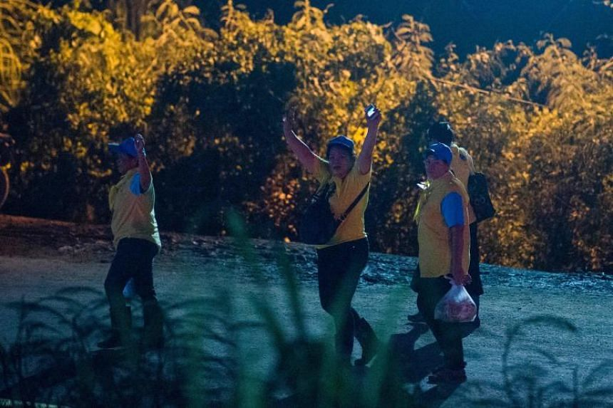 Thai volunteers celebrate while leaving the Tham Luang cave area as members of a youth football team and their coach were all rescued in the cave on July 10, 2018.