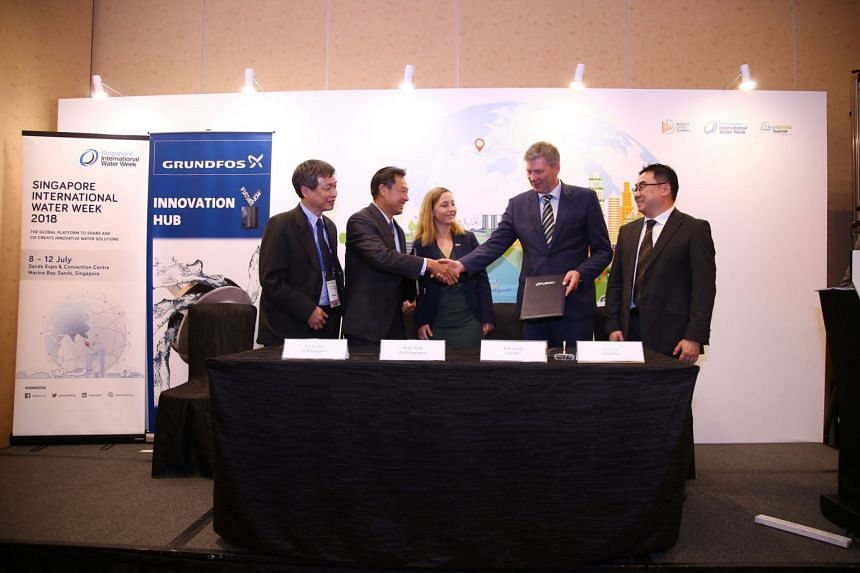 PUB chief executive Ng Joo Hee (second from left) shakes hands with Mr Kim Jensen, Grundfos' regional managing director for Asia-Pacific, at the MOU signing on the sidelines of Singapore International Water Week on July 10, 2018.