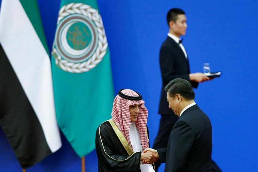 Chinese President Xi Jinping and Saudi Arabia's Foreign Minister Adel bin Ahmed Al-Jubeir shake hands at a China Arab forum at the Great Hall of the People in Beijing, on July 10, 2018.