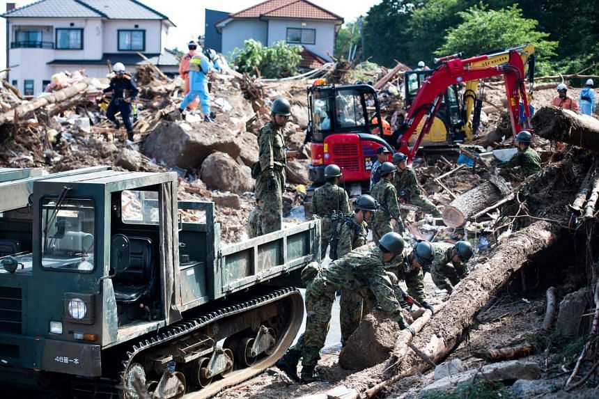 Rescuers and soldiers clear debris scattered on a street following a flood in Kumano, Hiroshima prefecture, on July 9, 2018.