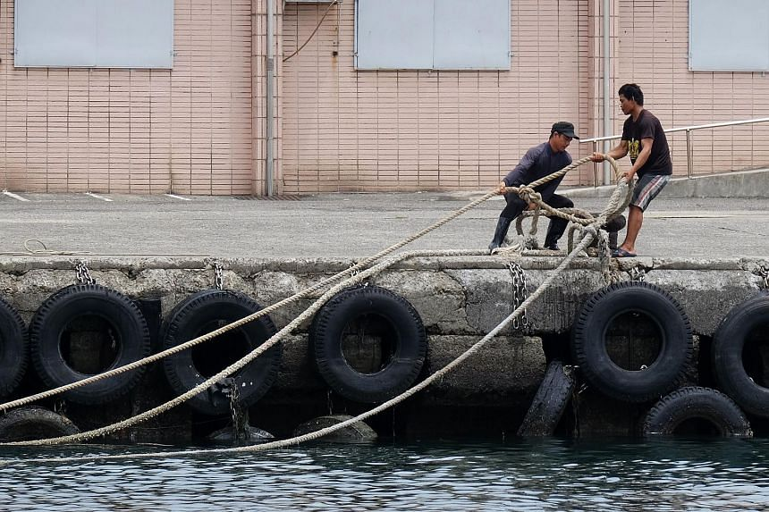 Workers securing ropes at the Patoutzu Fishing Harbour in Keelung on July 10, 2018, as boats come into dock ahead of the arrival of Typhoon Maria.