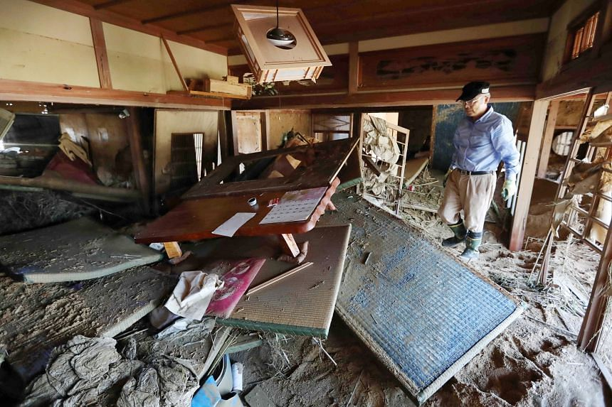 A man in his flood-destroyed home in Kurashiki, Okayama. About 10,000 people in 12 prefectures remain in evacuation centres.