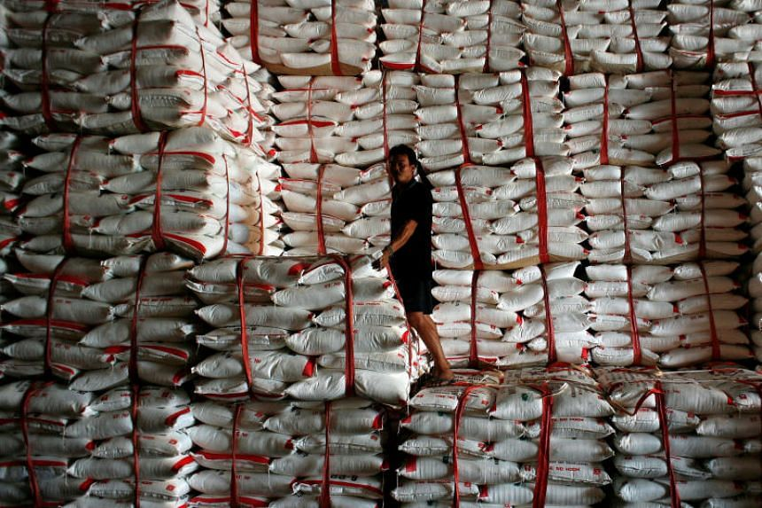 A worker stands atop sacks of refined white sugar at a factory in Baan Rai, Uthai Thani province, Thailand.