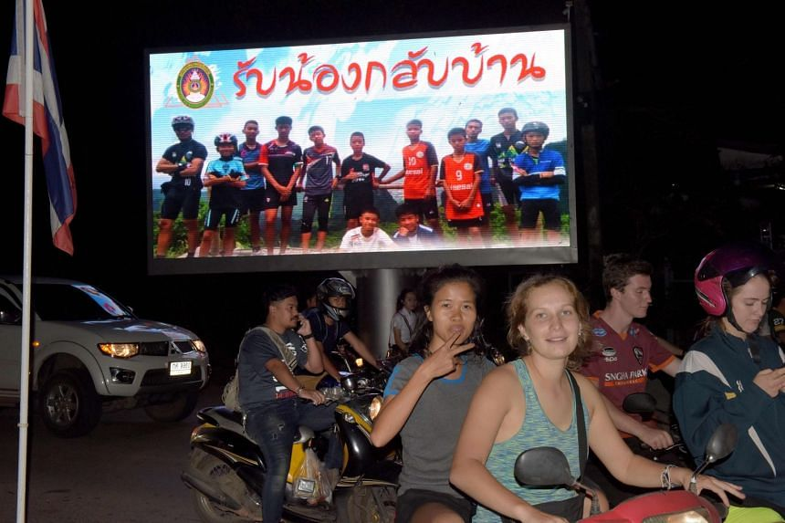 "Motorists in Chiang Rai pass a billboard with a photograph showing members of the Thai boys' team and their coach with a message ""welcome home brothers"" on July 10, 2018."