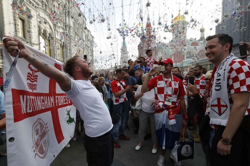 An England supporter cheers next to Croatia fans before the match in the city centre.