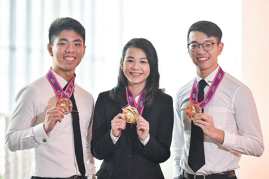 ITE College East student Shauna Tan with SIT students Lewis Tan (far left) and Toh Shu Han. Ms Tan is the first female to win in the Information Network Cabling category. Mr Tan and Mr Toh took the bronze medal in the Rapid Transit Systems category.