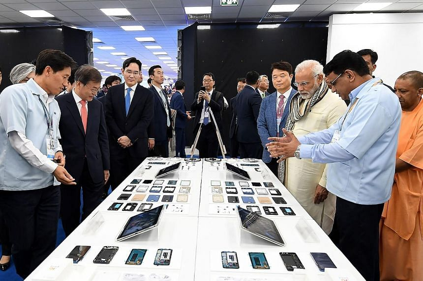 South Korean President Moon Jae-in (second from left) and Indian Prime Minister Narendra Modi (with scarf) visiting the world's largest smartphone factory opened by Samsung in the city of Noida, Uttar Pradesh, on Monday. The two countries inked 11 ag