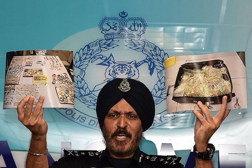 Malaysia's Commercial Crime Investigation Department director Amar Singh showing pictures of items seized from six premises linked to former premier Najib Razak, including cash and a stash of jewellery.