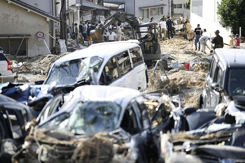 Debris caused by torrential rain being cleared in Aki ward in Hiroshima city in a photo taken by Kyodo yesterday. Hiroshima prefecture was the hardest hit in terms of the number of deaths - 59 - followed by Okayama with 54. The rain has stopped in th