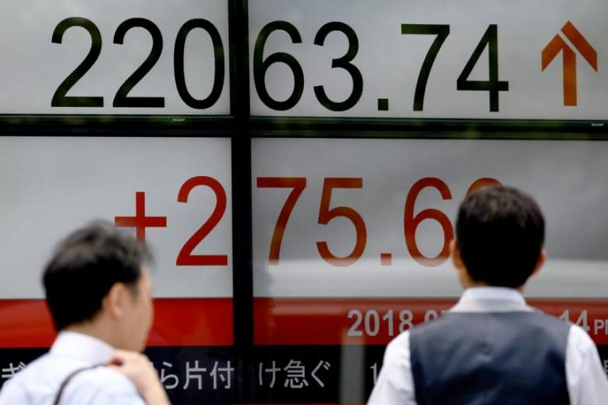 Pedestrians walk past an indicator for the numbers on the Tokyo Stock Exchange at a securities company in Tokyo, on July 9, 2018.