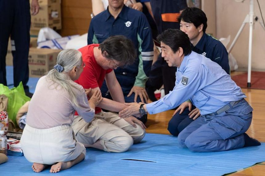 Japan's Prime Minister Shinzo Abe (right) visits a shelter for people affected by the recent flooding in Mabi, Okayama prefecture on July 11, 2018.