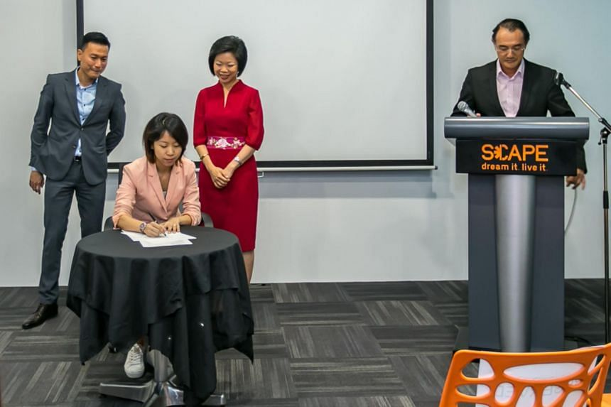 Ms Low Yi Juan, programme manager at Architects of Life, signing the memorandum of understanding, with guest-of-honour Ms Sim Ann (in red), Senior Minister of State for Culture, Community and Youth and of Communications and Information, looking on.