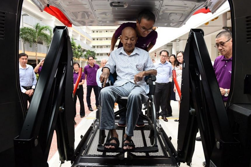 A Toyota HiAce bus refurbished and retrofitted with a fully-automatic hydraulic lifter by ComfortDelGro. 79-year-old wheelchair-bound senior Guek Chan Hong is the first to try this new lifter.