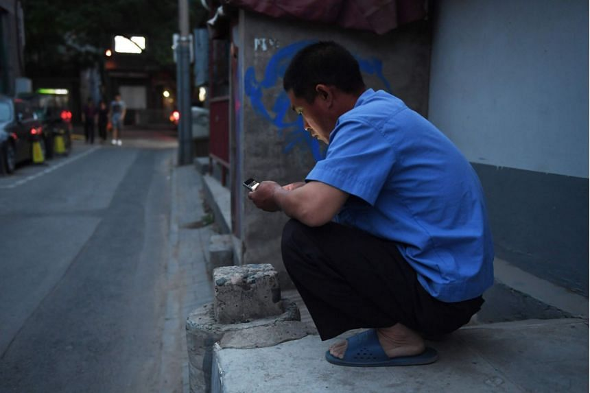 A man uses a mobile phone at an alley in Beijing, on June 15, 2018. Live-streaming platforms in China discovered their fan base with men as many migrated to big cities for jobs and sought human connection via the Internet.