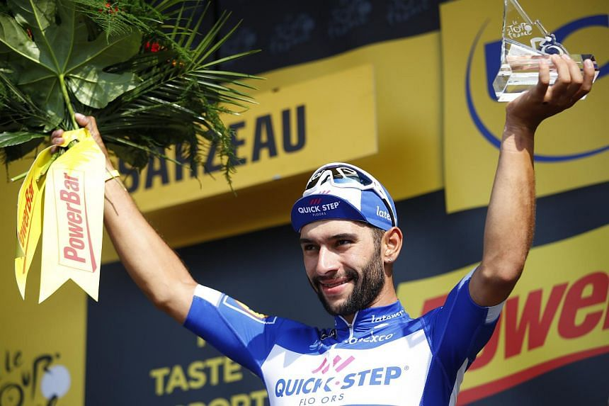 Quick Step Floors rider Fernando Gaviria celebrates on the podium after winning the 4th stage of the 105th edition of the Tour de France, on July 10, 2018.
